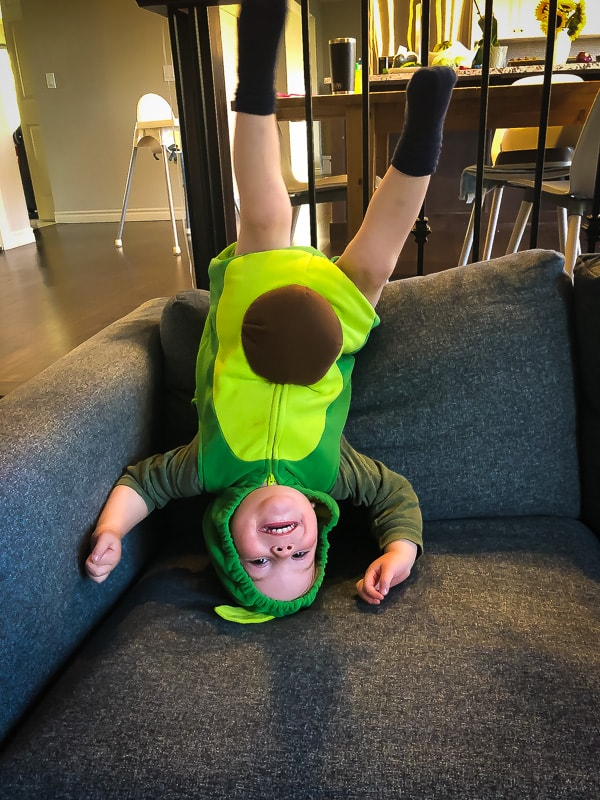 picture of a little boy in an avocado outfit upside down on the couch