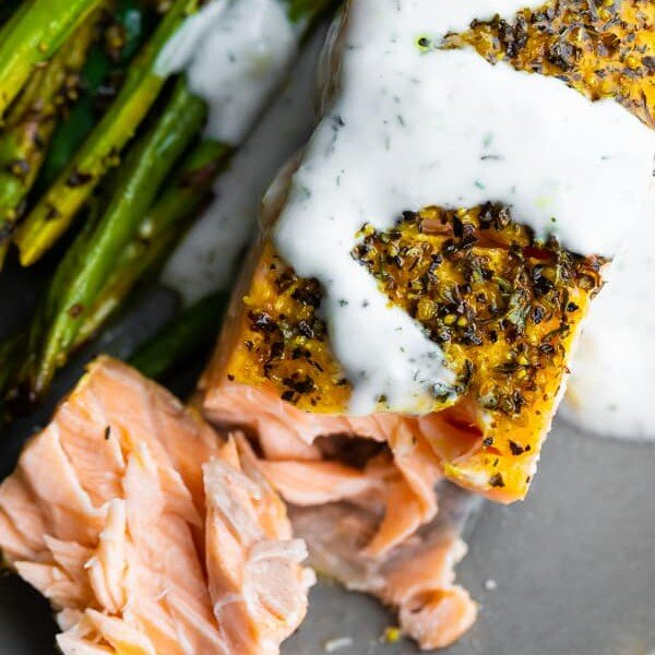 close up shot of baked lemon pepper salmon with asparagus on the side