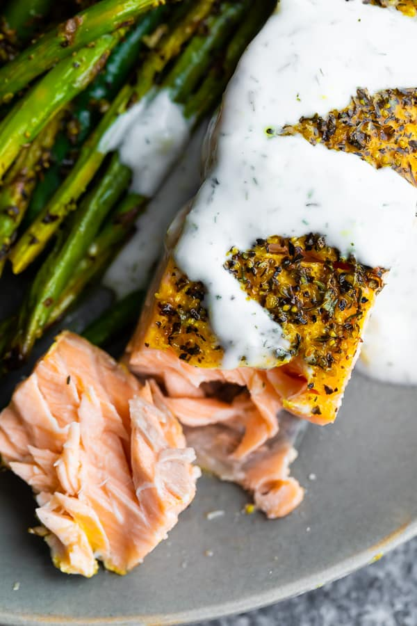 close up overhead shot of lemon pepper salmon drizzled with yogurt sauce