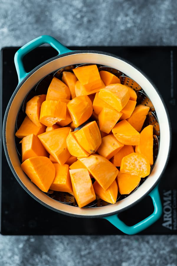 sweet potato chunks in steamer basket for healthy mashed sweet potatoes