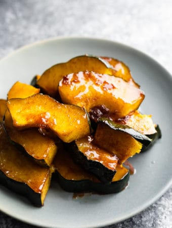 pile of maple butter roasted acorn squash on gray plate