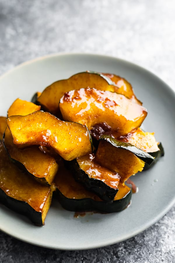 roasted acorn squash on grey plate with sticky glaze