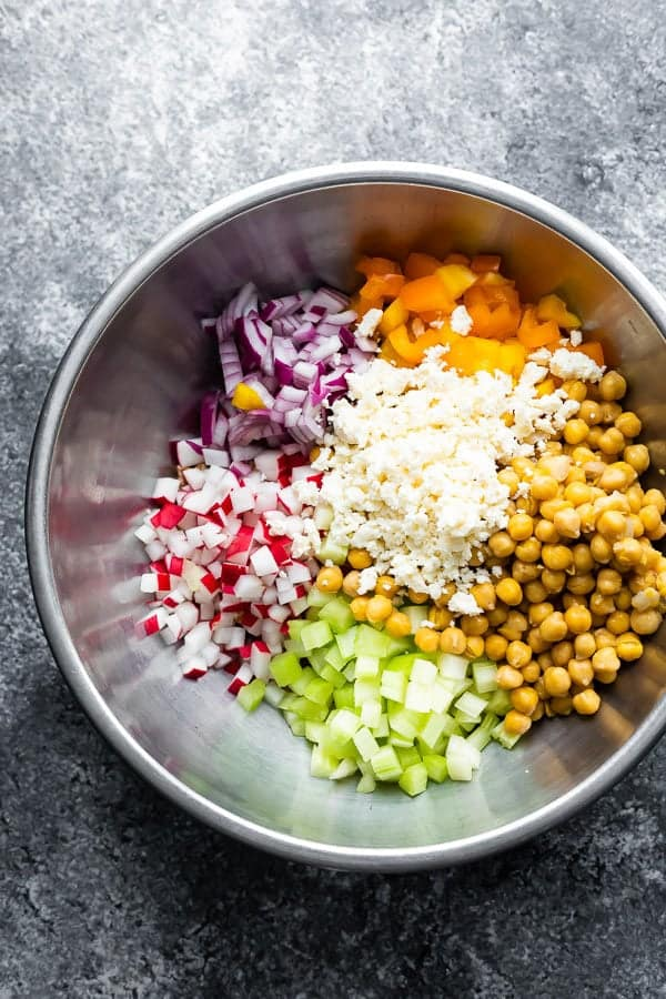 overhead shot of ingredients for chopped chickpea salad in large metal bowls