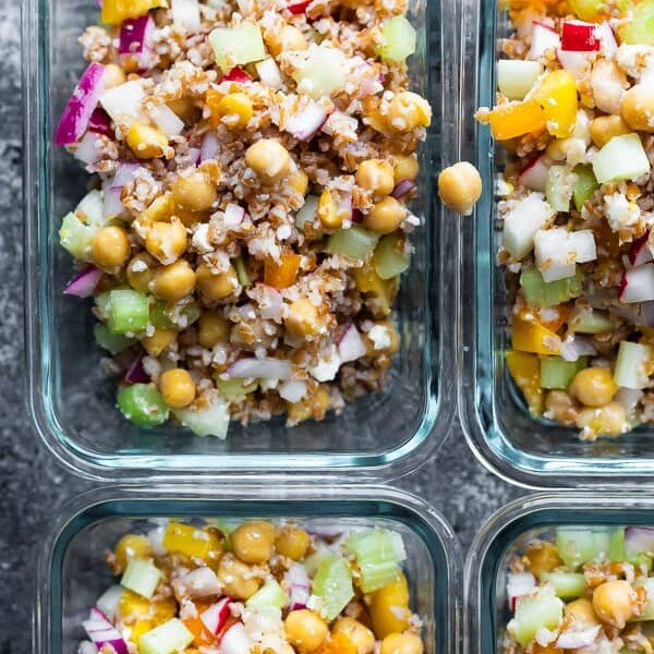 overhead shot of four glass meal prep container with chopped chickpea salad