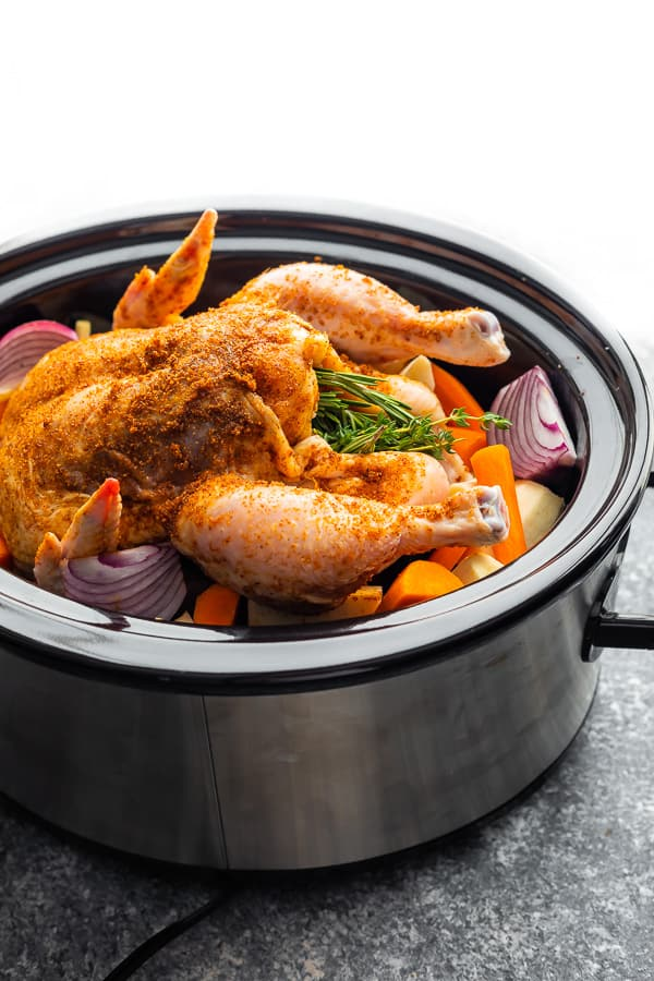 crockpot whole chicken and potatoes in slow cooker before cooking