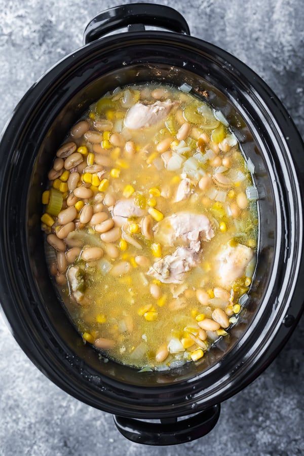overhead view of ingredients for white bean chicken chili crockpot in slow cooker after cooking