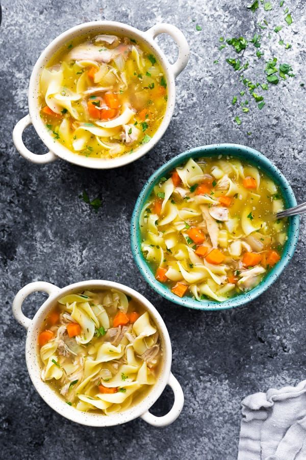 overhead view of three bowls of crockpot chicken noodle soup