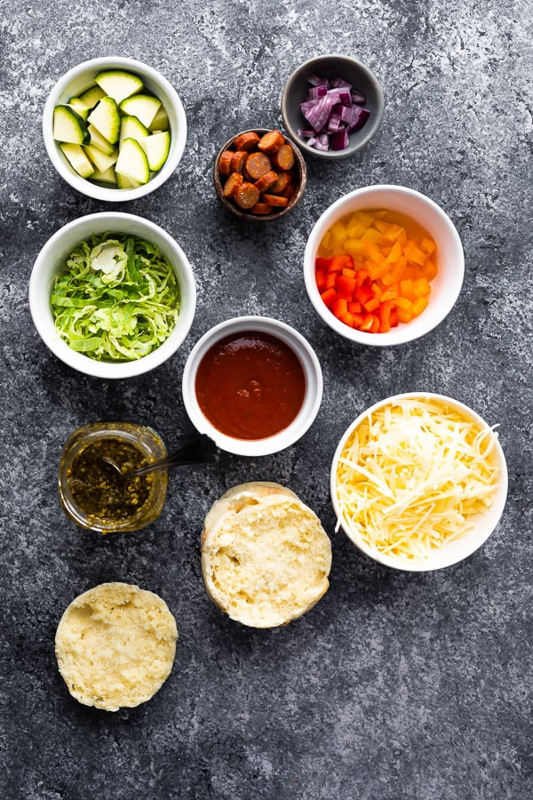 overhead view of ingredients needed for how to make english muffin pizzas