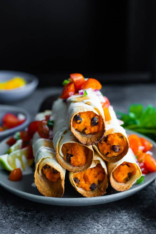 a stack of six black bean baked taquitos on a gray plate