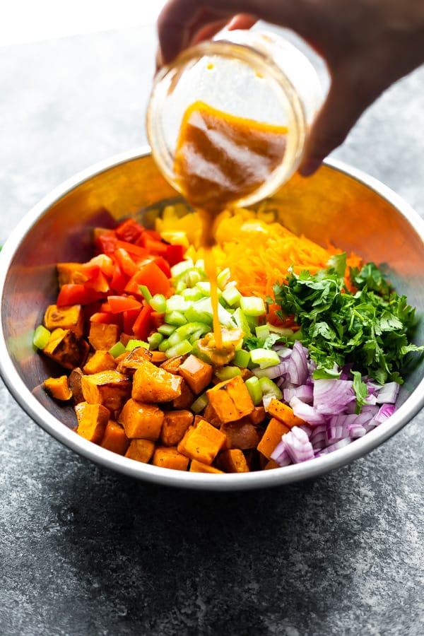 pouring vinaigrette over sweet potato salad