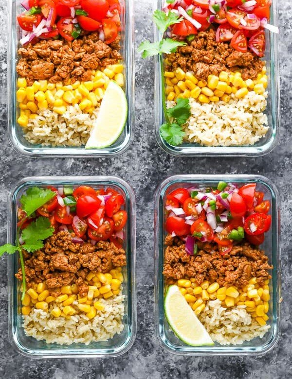 overhead shot of four containers filled with turkey taco meal prep bowls