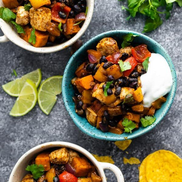 overhead shot of blue and white bowls filled with chili lime sweet potato and chicken skillet with fresh lime wedges, tortilla chips and cilantro