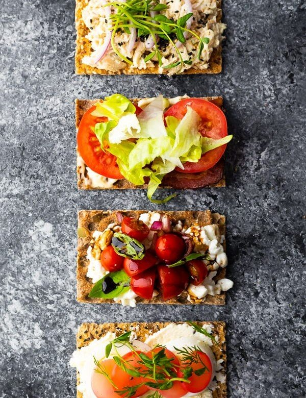 overhead shot of a variety of flat breads in a row with various ingredients on top