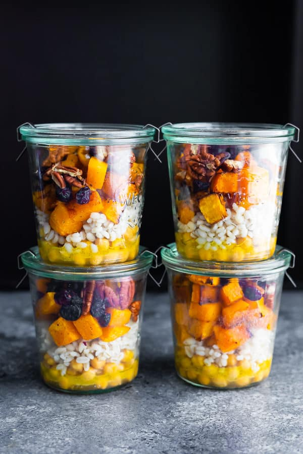 Stack of four glass jars filled with chickpea barley and butternut squash salad
