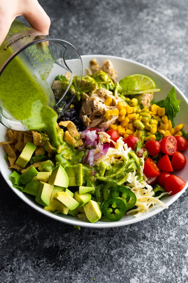 pouring cilantro vinaigrette over beer chicken taco salad