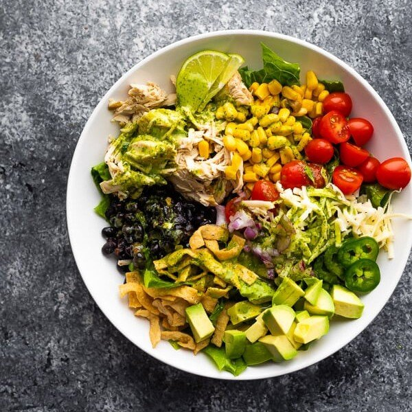overhead shot of beer chicken taco salad with cilantro vinaigrette in a white bowl on gray background
