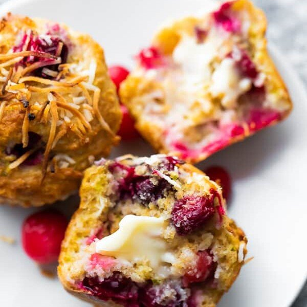 Coconut cranberry muffins cut in half on a white plate with butter on it