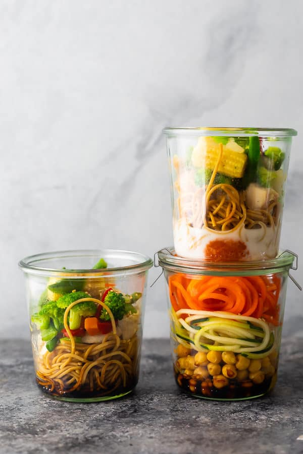Stack of three jars filled with healthy instant noodles and fresh veggies