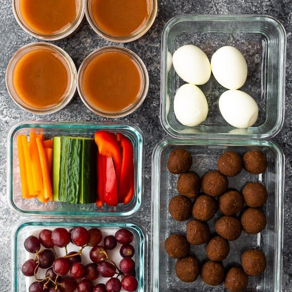 overhead shot of various foods in glass meal prep containers for kids snack drawer ideas