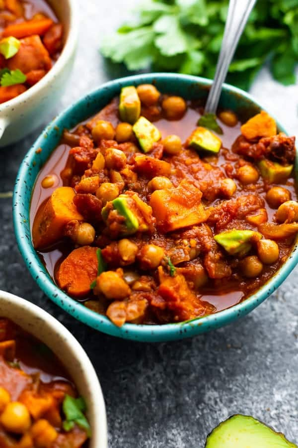 spicy slowcooker chickpea chili in a blue bowl with a spoon