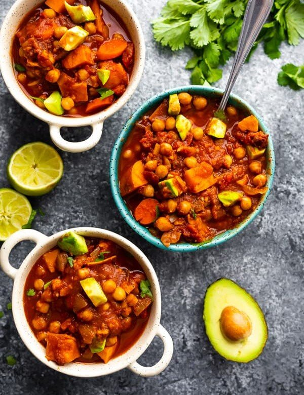 overhead shot of spicy slow cooker chickpea chili with white and blue bowls with fresh limes and avocado on gray background
