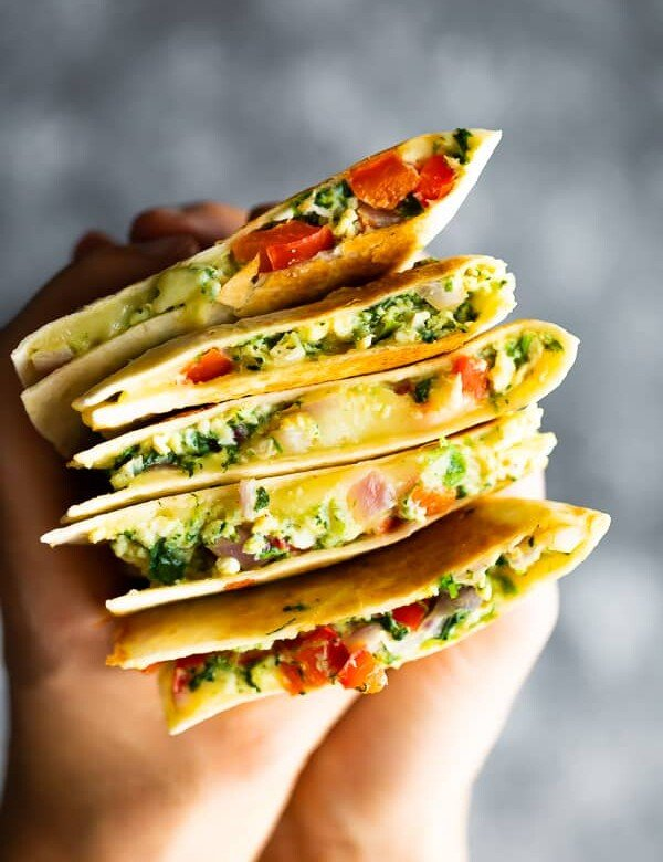 hand holding a stack of spinach and feta breakfast quesadilla slices