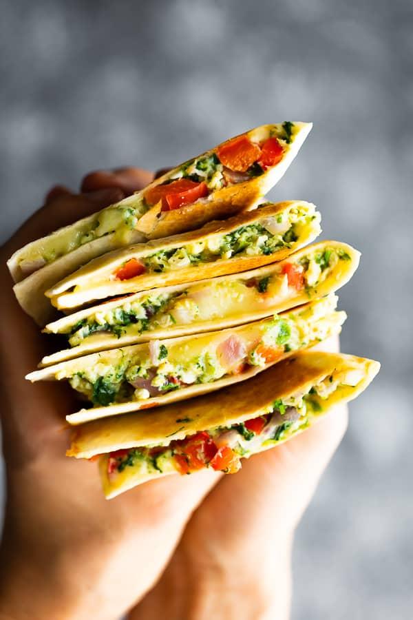 Hand holding five spinach feta breakfast quesadillas