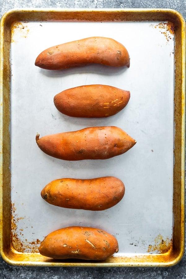 sweet potatoes on baking sheet for stuffed sweet potato recipe