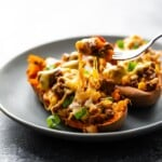 Two taco stuffed sweet potatoes on a gray plate with fork taking a bite