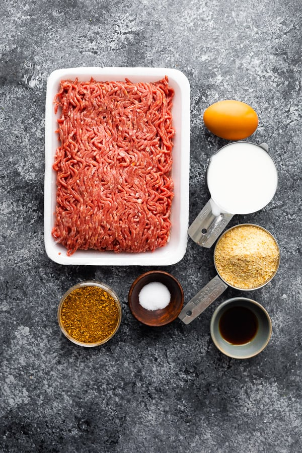 a pound of raw lean ground beef next to Moroccan spices in measuring cups