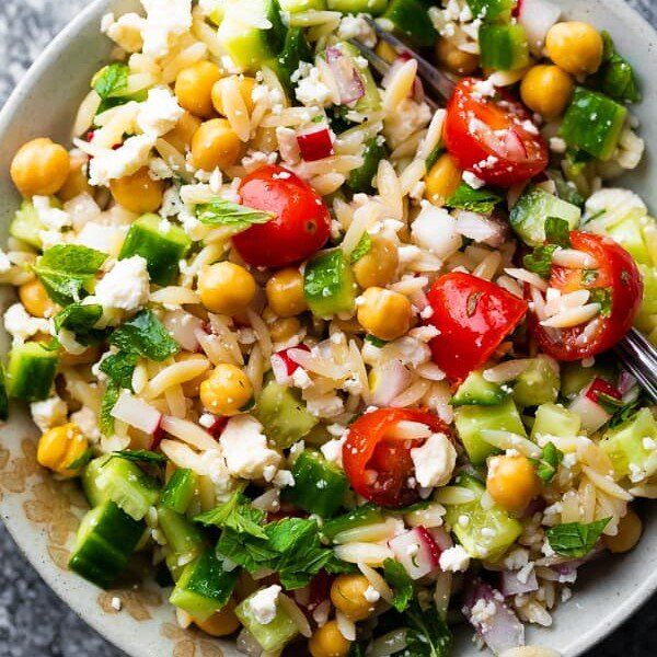 Orzo pasta salad with mint and feta in white bowl