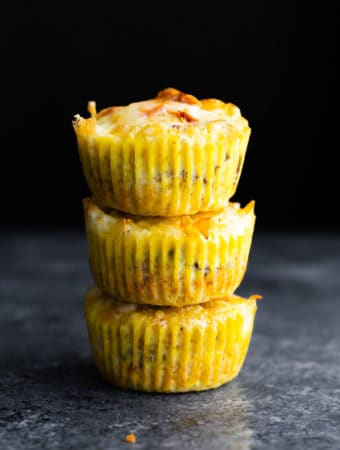 stack of three quinoa egg muffins on gray background