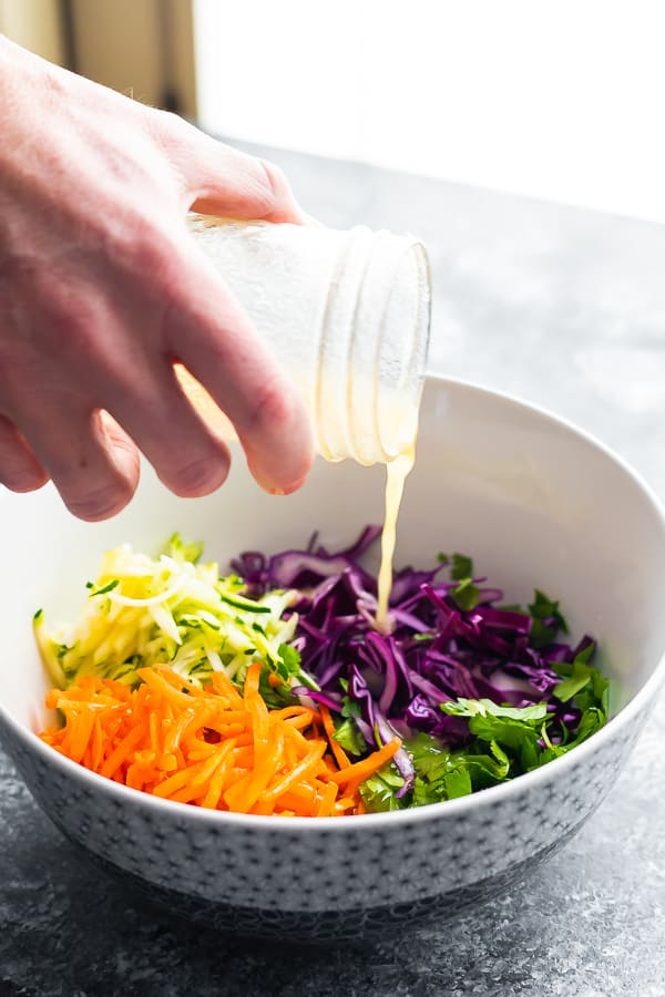 pouring vinaigrette over slaw ingredients