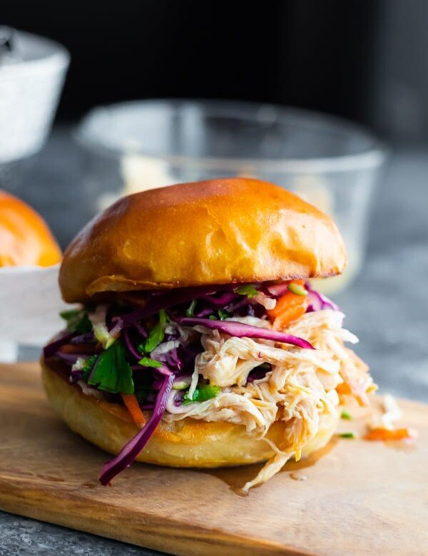 A close up of honey lime shredded chicken sandwich on a wood cutting board