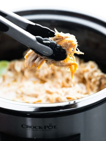 Honey lime chicken in the slow cooker with pair of tongs pulling some out