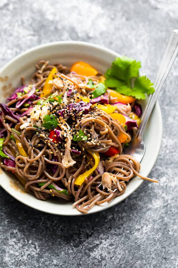 overhead shot of asian chicken soba noodle salad in white bowl with a fork