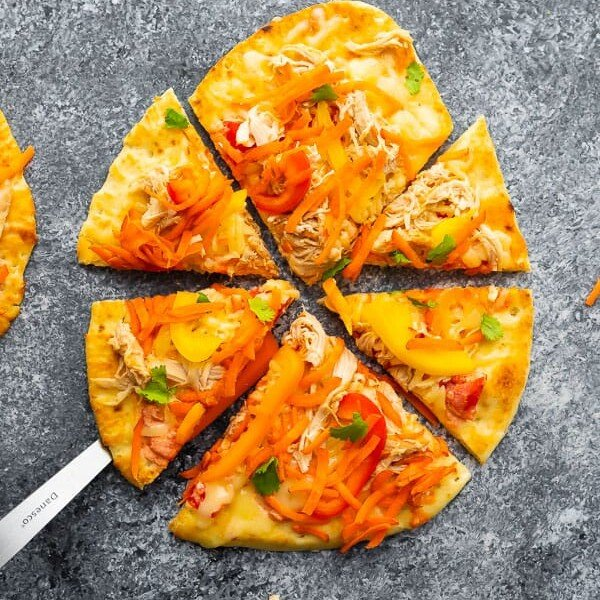 Overhead shot of thai chicken naan pizza cut into wedges on gray background