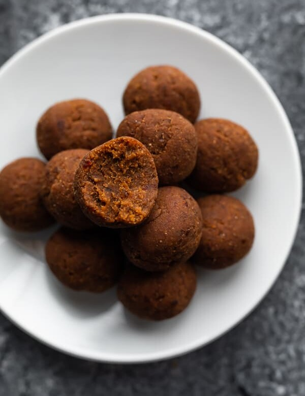 A pile of coconut date balls on a white plate with a bite taken out of one