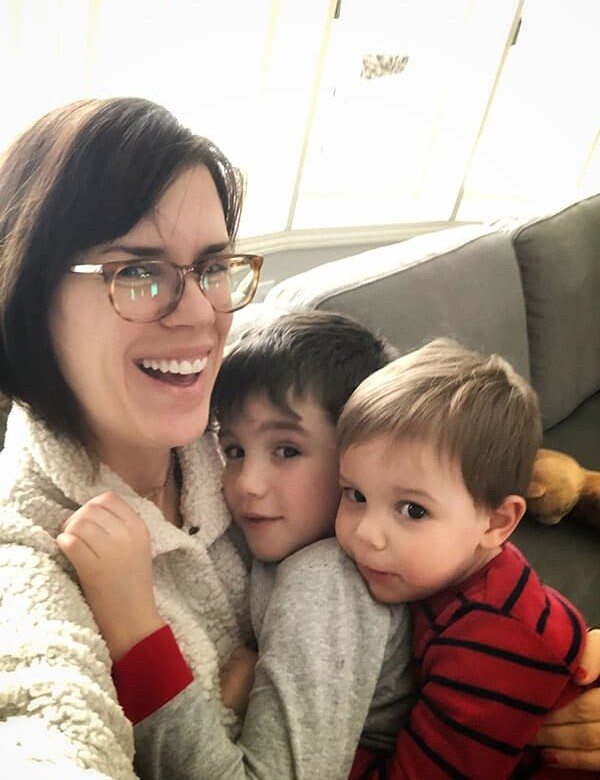 Denise holding her two sons on the couch