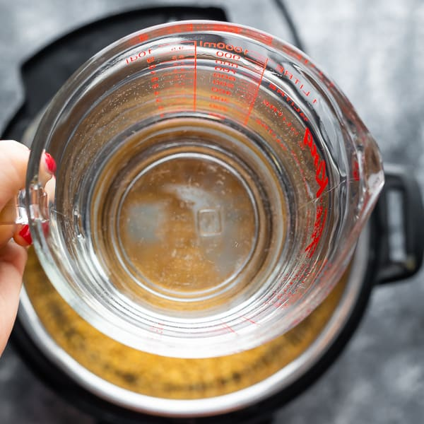 water in measuring cup over instant pot