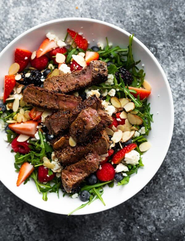 overhead shot of strawberry steak salad in a large white bowl on gray background
