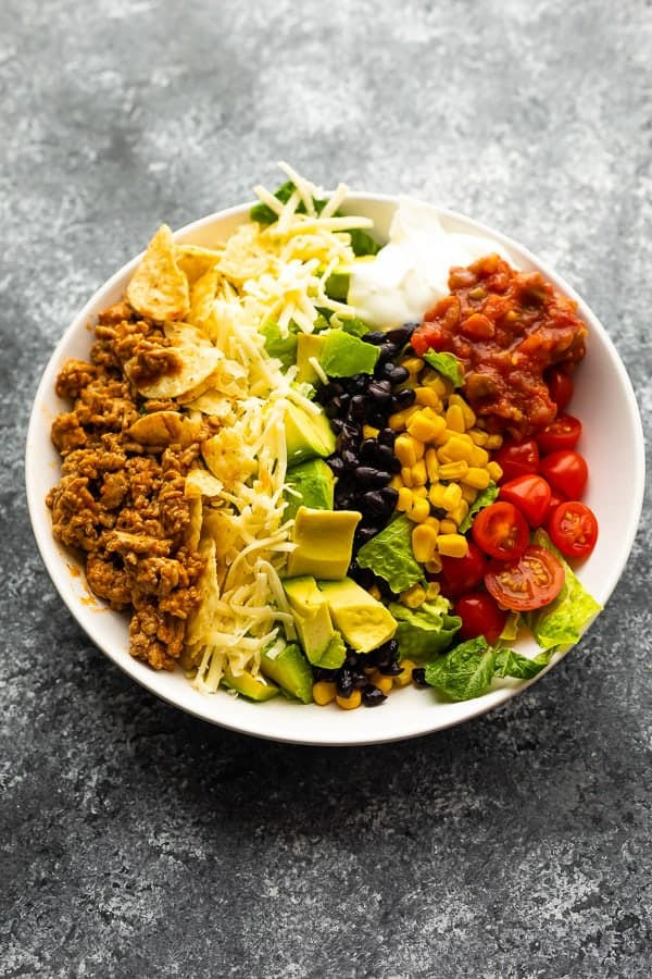 Healthy taco salad in a large white bowl on gray background
