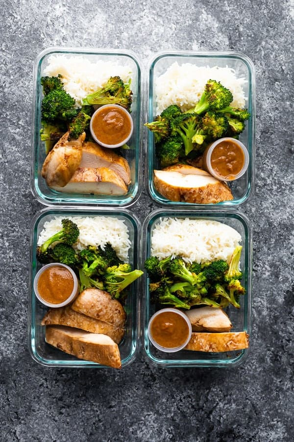 overhead shot of four glass meal prep containers filled with thai chicken lunch bowls