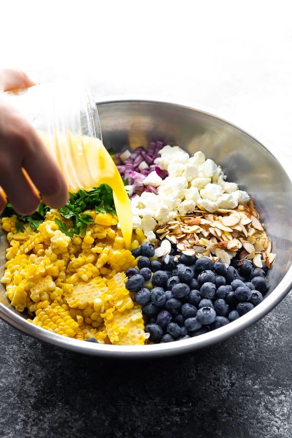 pouring vinaigrette onto the corn barley salad
