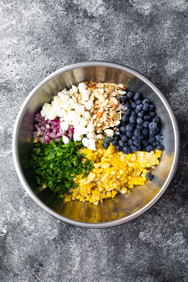 bowl with barley corn salad ingredients before tossing in vinaigrette