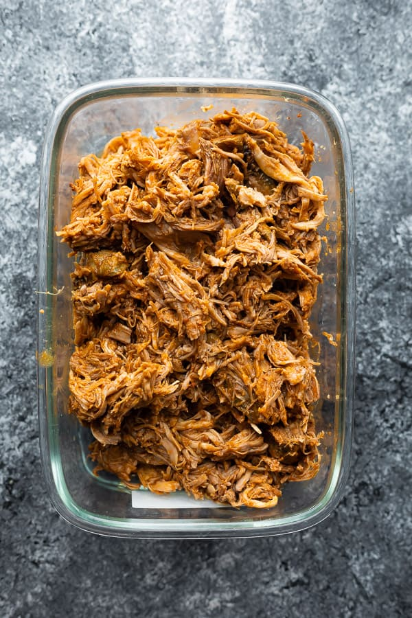 crock pot pulled pork in a large glass meal prep container for storage