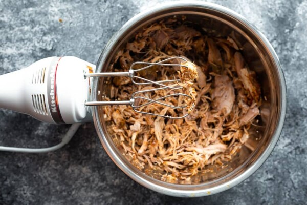 shredded pork in bowl with electric hand mixer sitting beside it