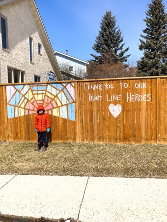 A child standing in front of a wooden fence