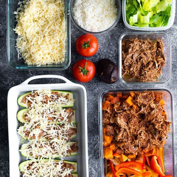 overhead shot of multiple meal prep containers and fresh produce for pulled pork meal prep plan