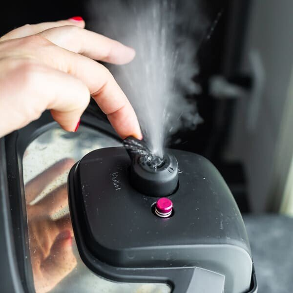 Picture of a hand releasing the pressure on an instant pot